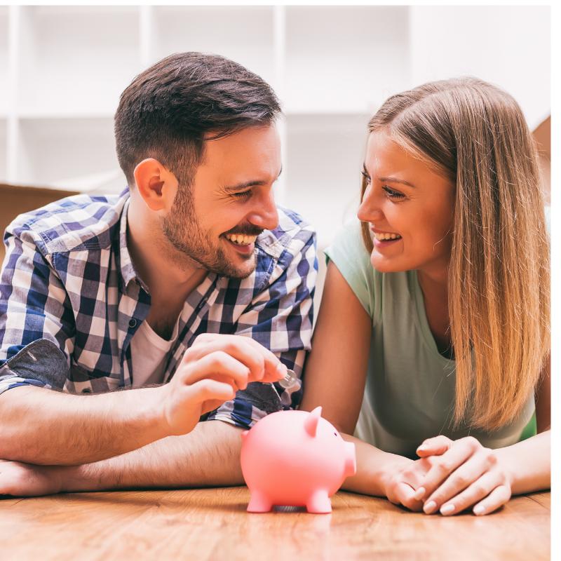 Couple lying on ground putting money into piggy bank